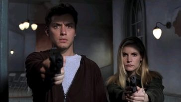 A close-up shot of Ted Pikul (Jude Law) and Allegra Geller (Jennifer Jason Leigh) aiming their handguns towards the camera