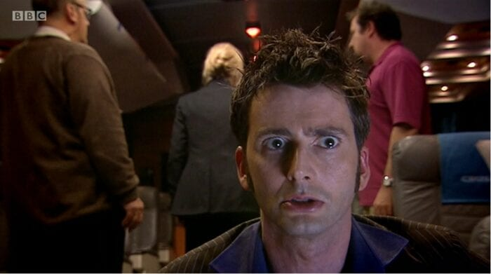 The Doctor crouches in the foreground, rendered immobile, while the other passengers stand in the background with their backs to him.