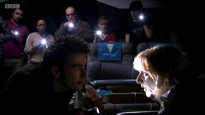 The Doctor converses with a possessed Sky while the other passengers hide behind seats, shining torches at her.