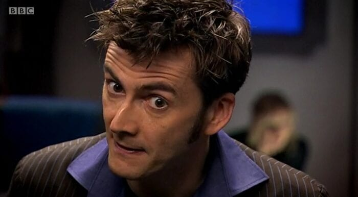 The Doctor looks agitated in a close up, while an unfocused Sky crouches in the background.