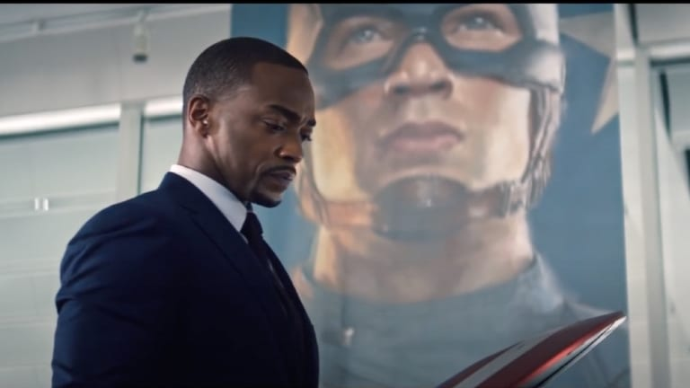 Sam Wilson (Falcon) reckons with Steve Rogers' legacy as he stands in front of a mural of him and looks down at the Captain America shield