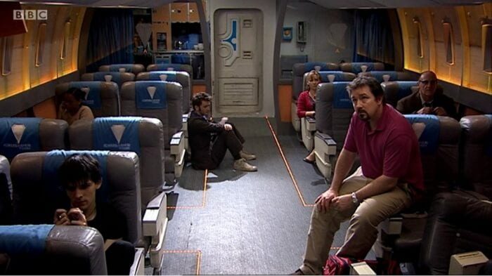 Every passenger on the bus sits in separate areas, the Doctor slouched in the aisle.