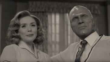 Wanda stands next to Vision in front of a window, in black and white