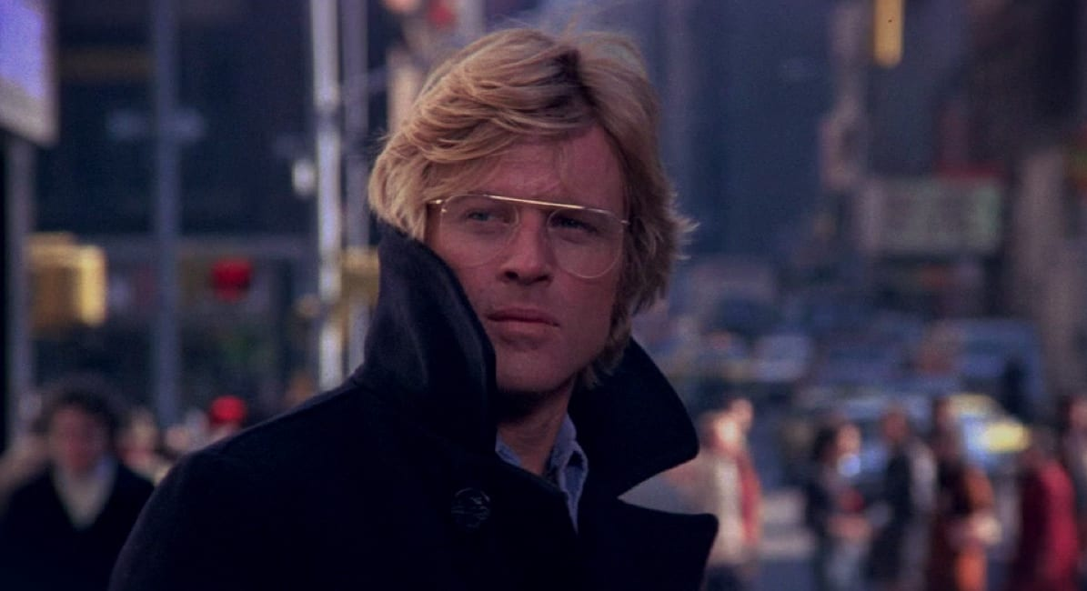 Robert Redford's Joe Turner is a quixotic survivalist, as he looks on wearing thin-framed glasses on a busy street that is out of focus behind him
