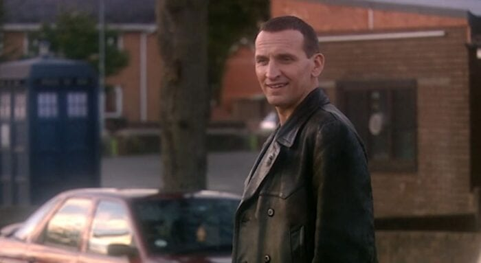 The Doctor standing on the street in his leather jacket
