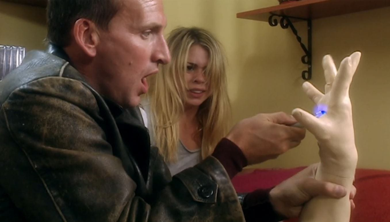 The Doctor uses his sonic screwdriver on a plastic hand as Rose looks on