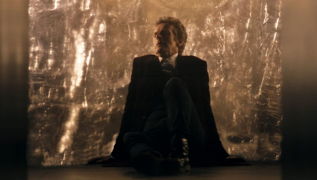 The Doctor sits on the floor by the spantium wall in Doctor Who Heaven Sent