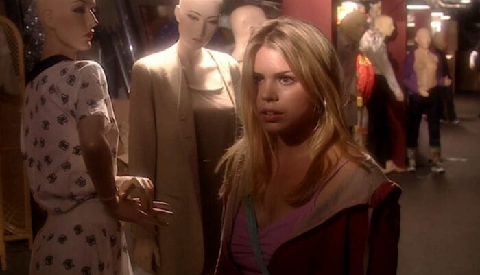 Rose stands in front of mannequins with her face half in the shadows