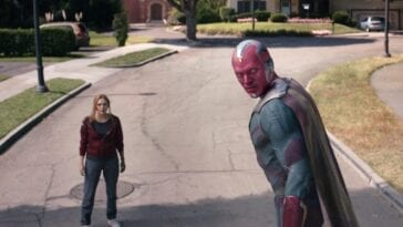 Vision looks over his shoulder as Wanda looks on, standing in the street, in WandaVision 'The Series Finale'