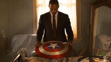 The Falcon looks down at the Captain America shield on a table