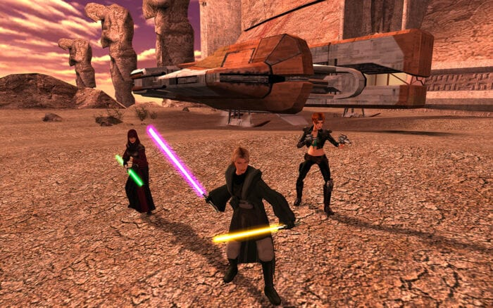 KOTOR 2 screenshot featuring the party; a jedi in grey robes with two lightsabers, another jedi with a double blade green saber, and a gunslinger with two pistols