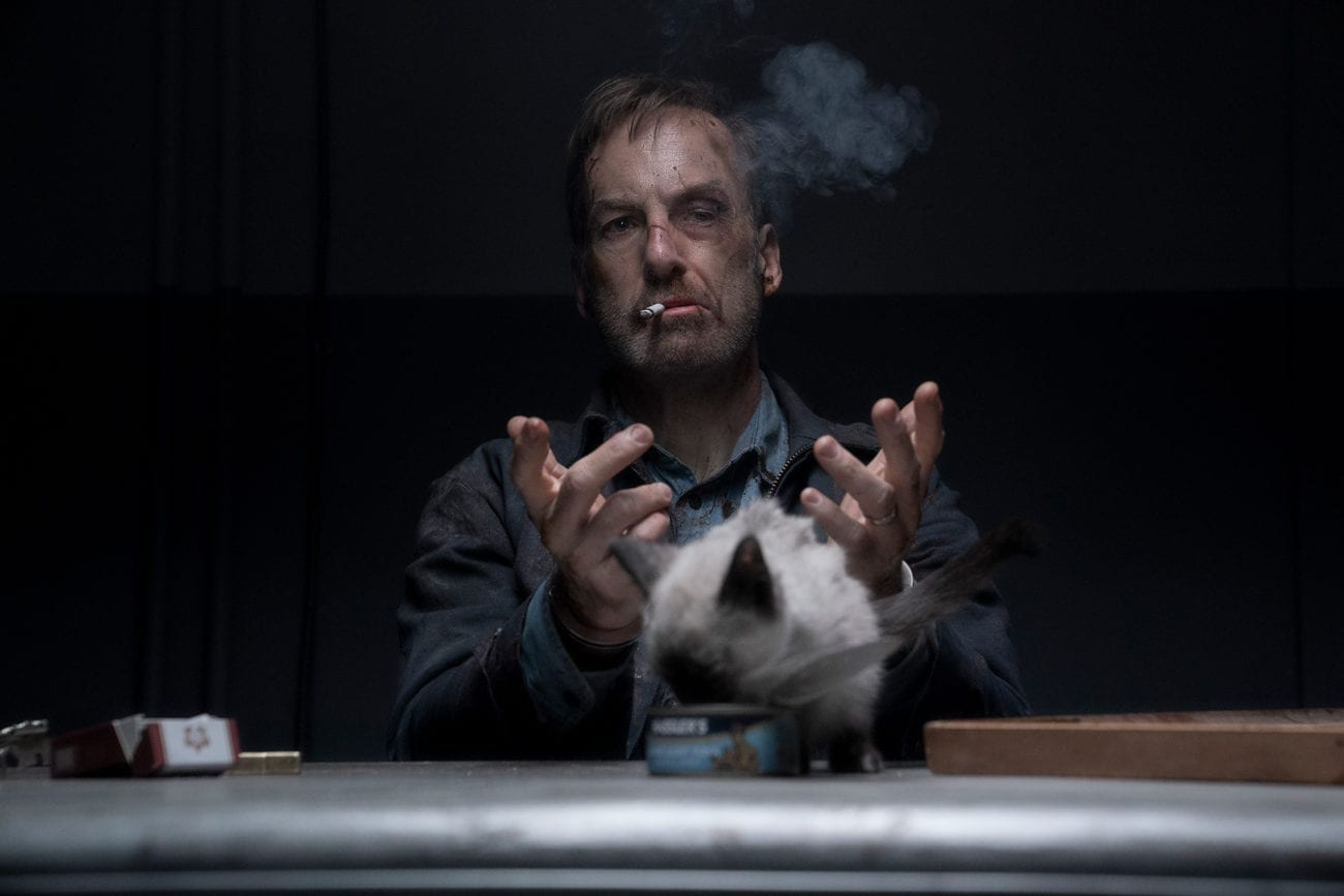 Hutch lets go of a cat to step forward and eat while he is handcuffed and smoking a cigarette.