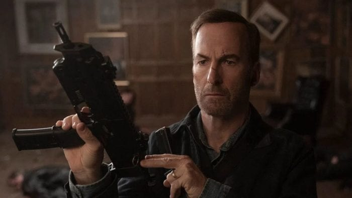 Hutch holds and cocks back a submachine gun.