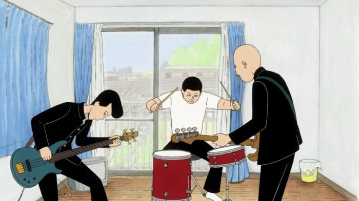 Ôta and Kenji play bass in the foreground while Asakura plays drums behind them in an otherwise empty room with a sliding glass door