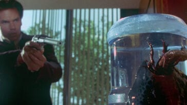 Sam Nivens points a gun at an alien on a water cooler