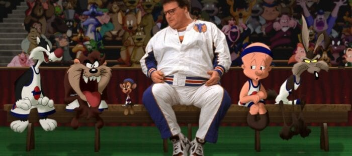 Wayne Knights sits in the middle of several Looney Tunes characters during the basketball game. They are all wearing uniforms