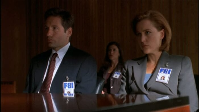 Mulder (David Duchovny) and Scully (Gillian Anderson) at an FBI tribunal...