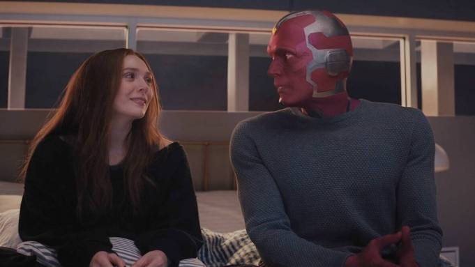 Wanda Maximoff looks at Vision while sitting on a bed