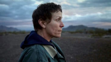Frances McDormand stares into open space, surrounded by mountains and dirt roads