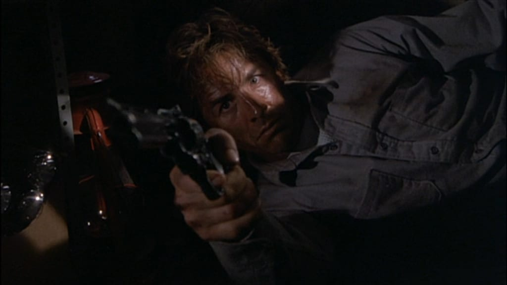 Jerry Beck on his side, holding his revolver out