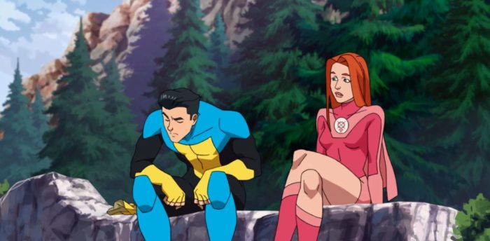 Atom Eve and Invincible sit on a ledge over a waterfall.