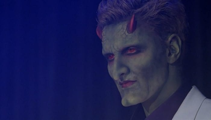 """Lorne (green skin, little red horns, red eyes, snazzy suit) on stage in his first appearance in """"Judgement"""""""