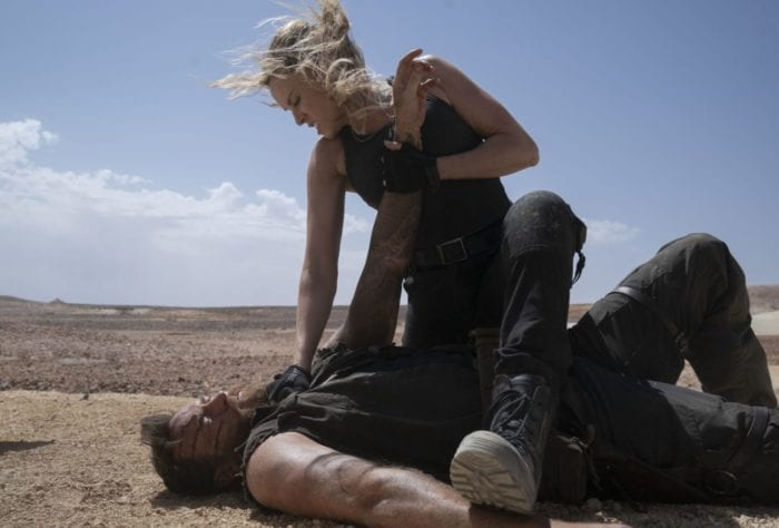 Sonya Blade restrains Kano on the ground.