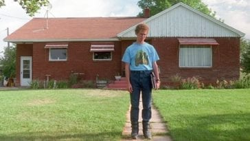 Napoleon (Jon Heder) standing outside his house. He is wearing puffy boots and a blue shirt with horses on it tucked into his jeans. The lawn is freshly cut and the russet roof of the brick home is cast in sunlight.