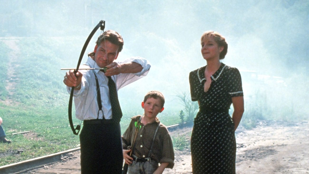 Truman using a bow and arrow in front of his wife and child