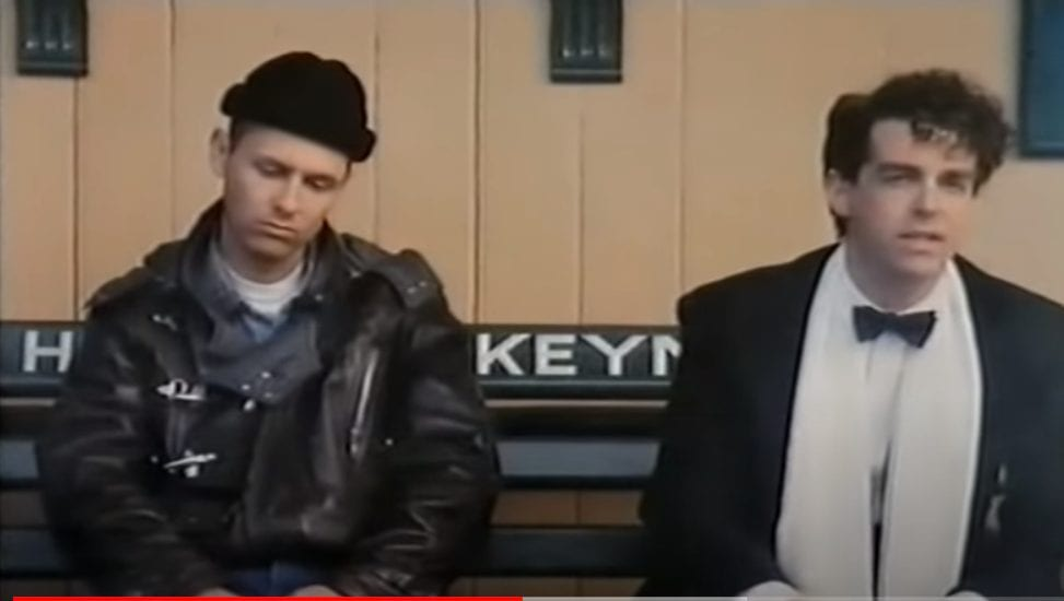 Two men sitting on a bench. On the left Chris Lowe (Pet Shop Boys) in a black wool cap and leather jacket, looking down pensively. On the right Neil Tennant (Pet Shop Boys) in tuxedo, black bowtie and a scarf, singing.