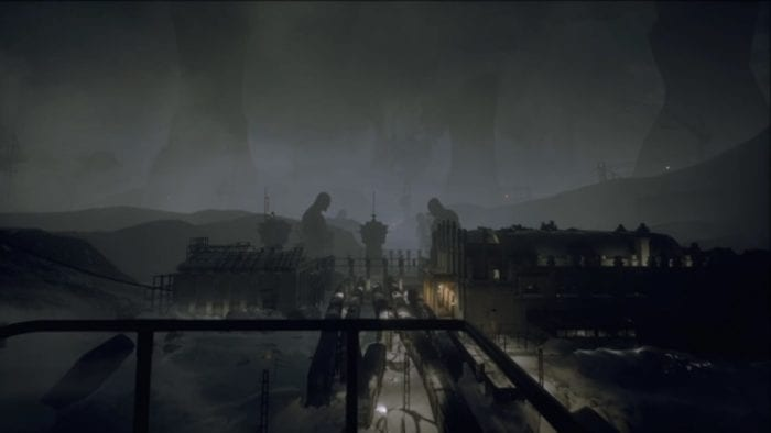 view of an underground train yard with giant distant statues looming over the trains
