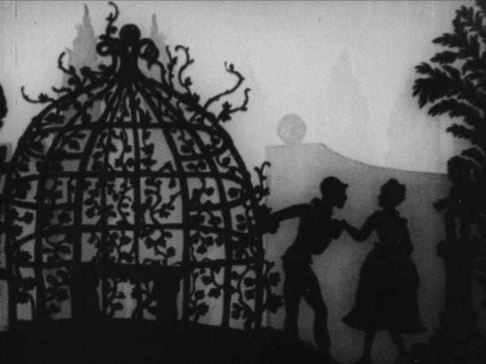 Still from Lotte Reiniger's Harlequin. The silhouette cutouts stand in front of an ornate dome in a garden.