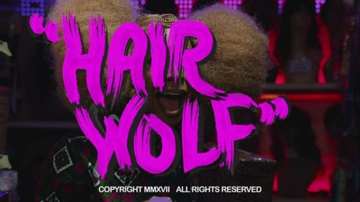 """Title card from Hair Wolf. The words """"Hair Wolf"""" are overlayed over a screaming woman. The words are bright pink and look like they were written in finger paints."""
