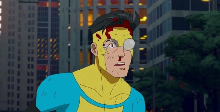 Invincible is stunned after being punched by Omni-man into downtown Chicago. His face and nose are bloody, and one of the lenses on his costume has shattered.