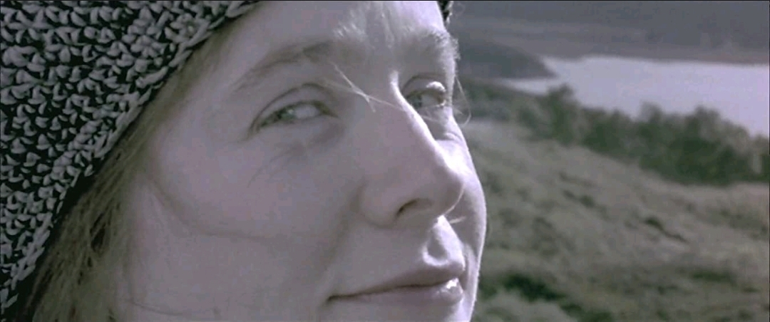 A close-up shot of Bess McNeill (Emily Watson) looking directly at the camera