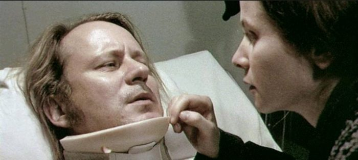 Bess leans over Jan in his hospital bed