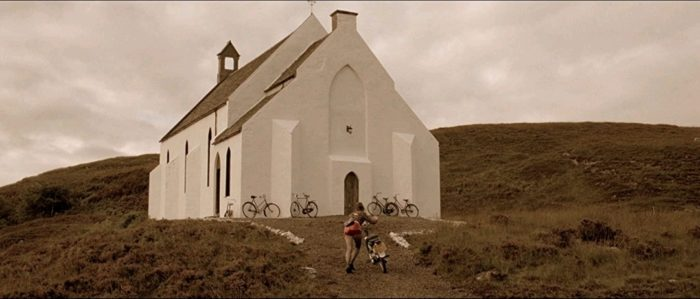 A white church sits surrounded by grass and a hill behind it, with bicycles out front