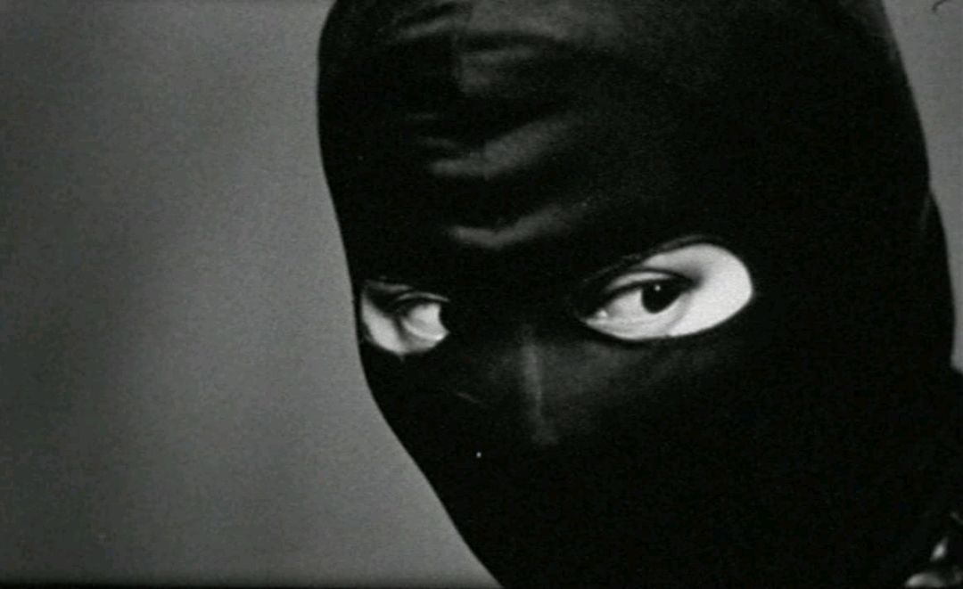 A close-up black and white shot of Maggie Cheung's masked face looking towards the right of the camera frame