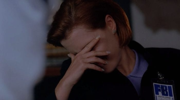 Scully puts her head in her hand, clearly exhausted at having to put up with Mulder's ridiculous theories
