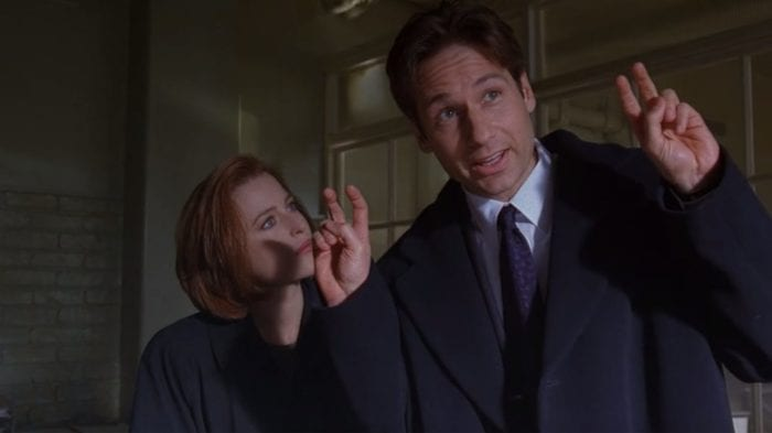 Scully and Mulder stood in the funeral home, Mulder mocking Scully's 'theories' with air quotations while she looks on irritably