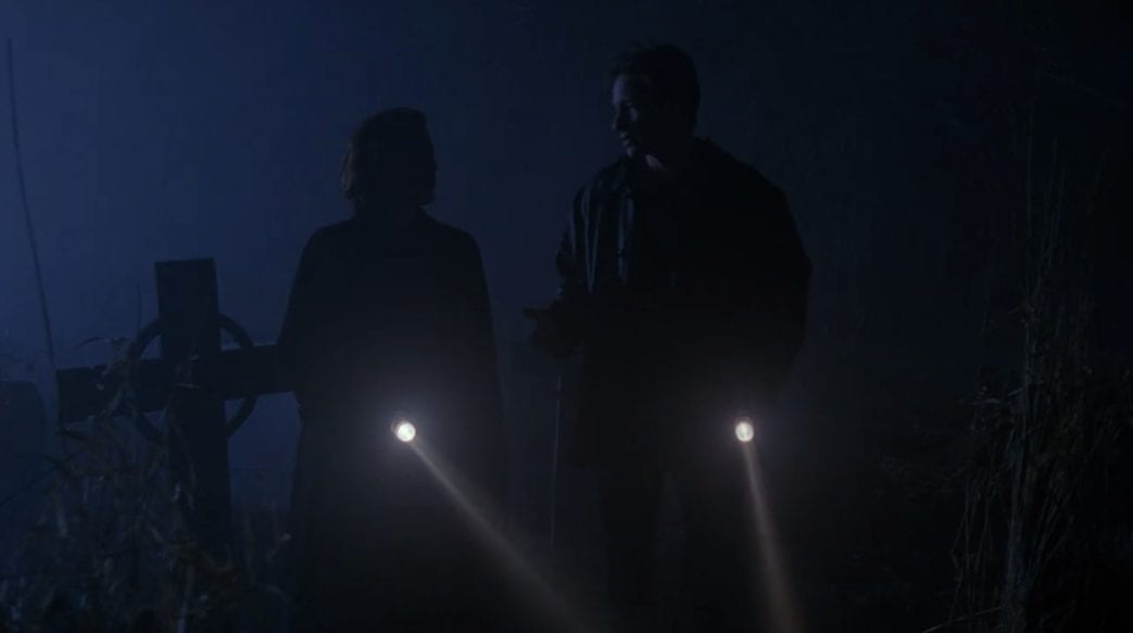 Scully and Mulder walk through the graveyard at night, torches lighting up the way