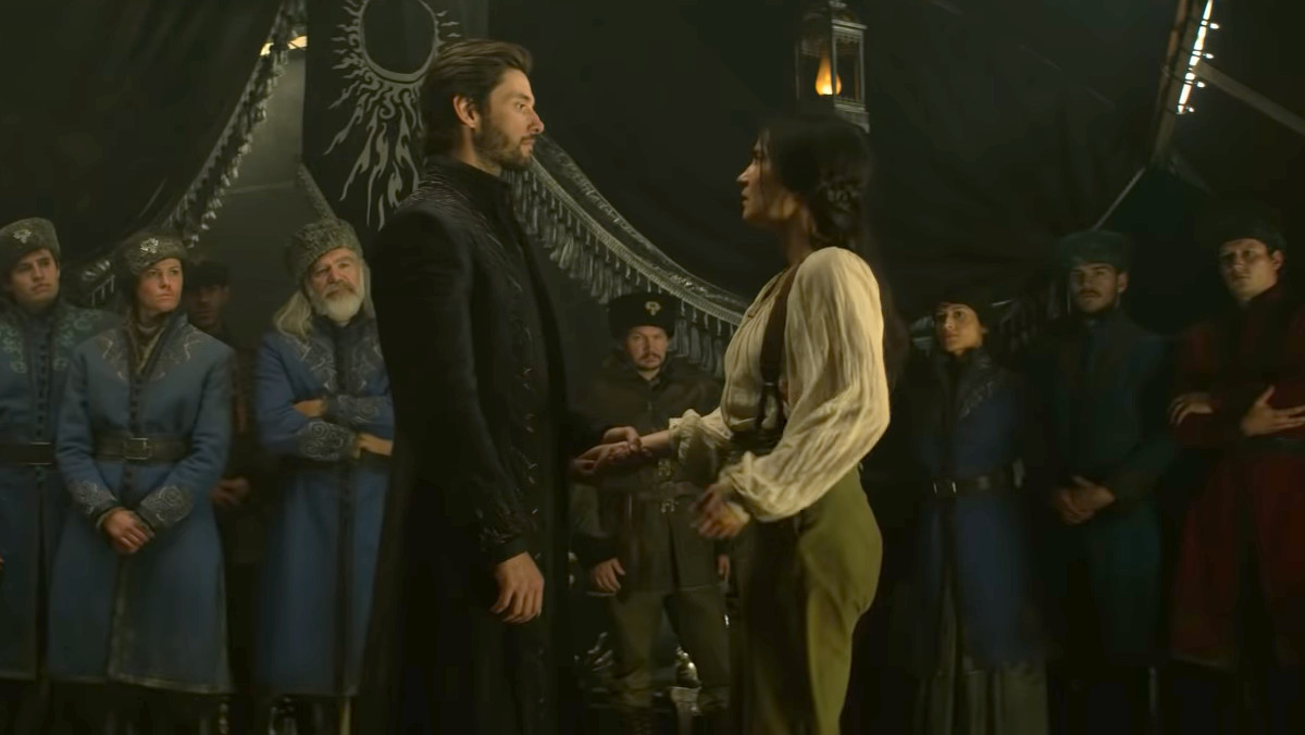 General Krigan (Ben Barnes) and Alina (Jessica Mei Li) stand looking at each other in front of a group of 2nd Army troops