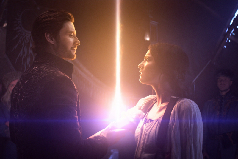General Krigan (Ben Barnes) looking into Alina's (Jessica Mei Li) eyes as a giant spark of light emanates from her wrist