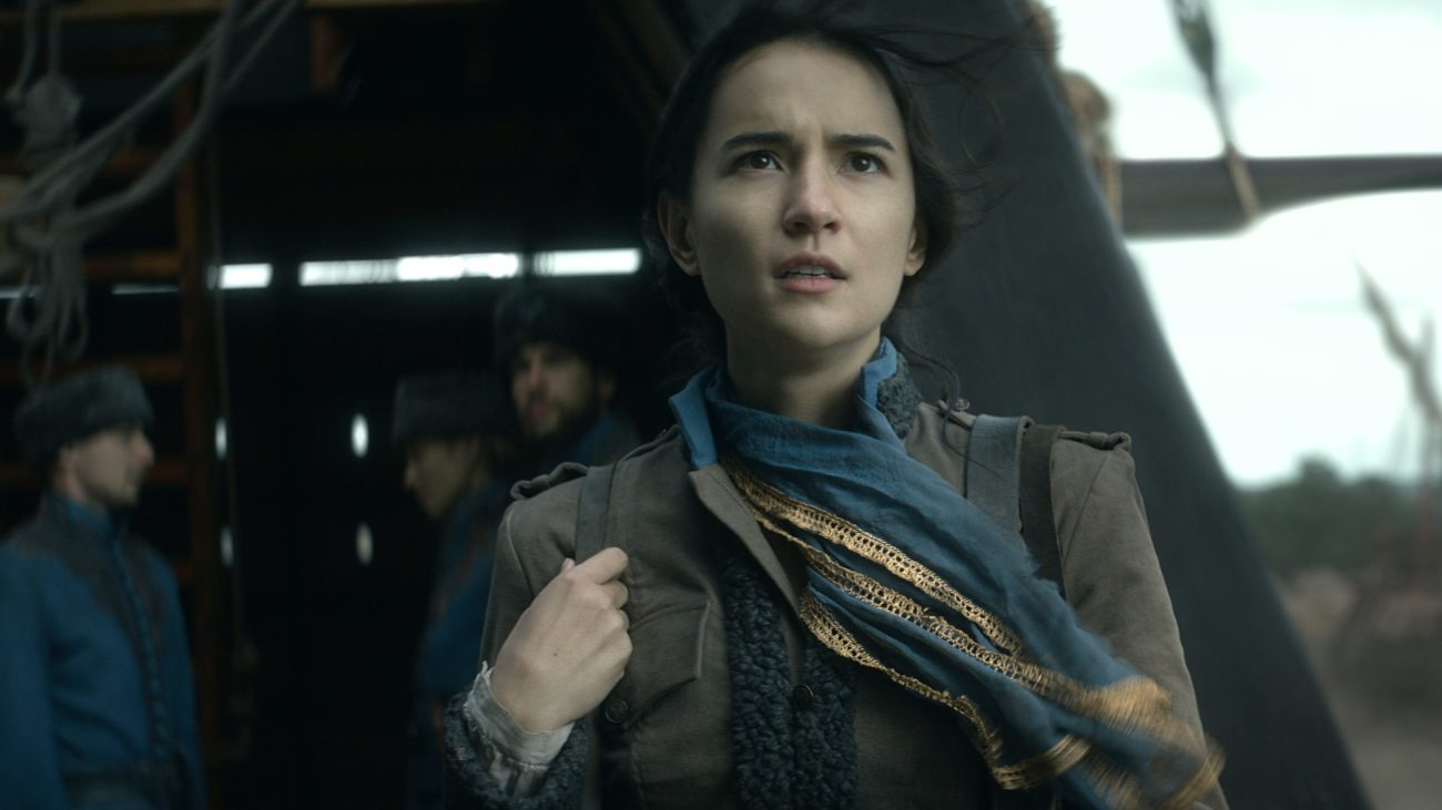 Alina (Jessica Mei Li) stands looking off to the sky with her scarf blowing in the breeze