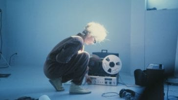Maryanne Amacher crouches on the ground in front of a tape player and oscillator.