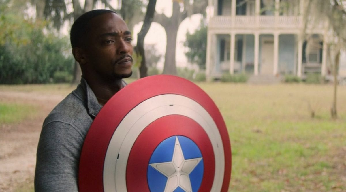 Sam stands holding the Captain America shield in front of him on a lawn