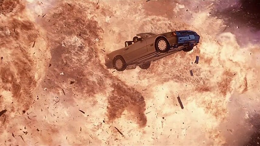 A Mercedes flying through the air surrounded by fire