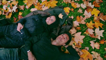Gabriela and Ethan lie on a leafy field looking up at the sky