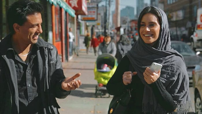 Ethan and Sahar smile as they walk down a street in Toronto