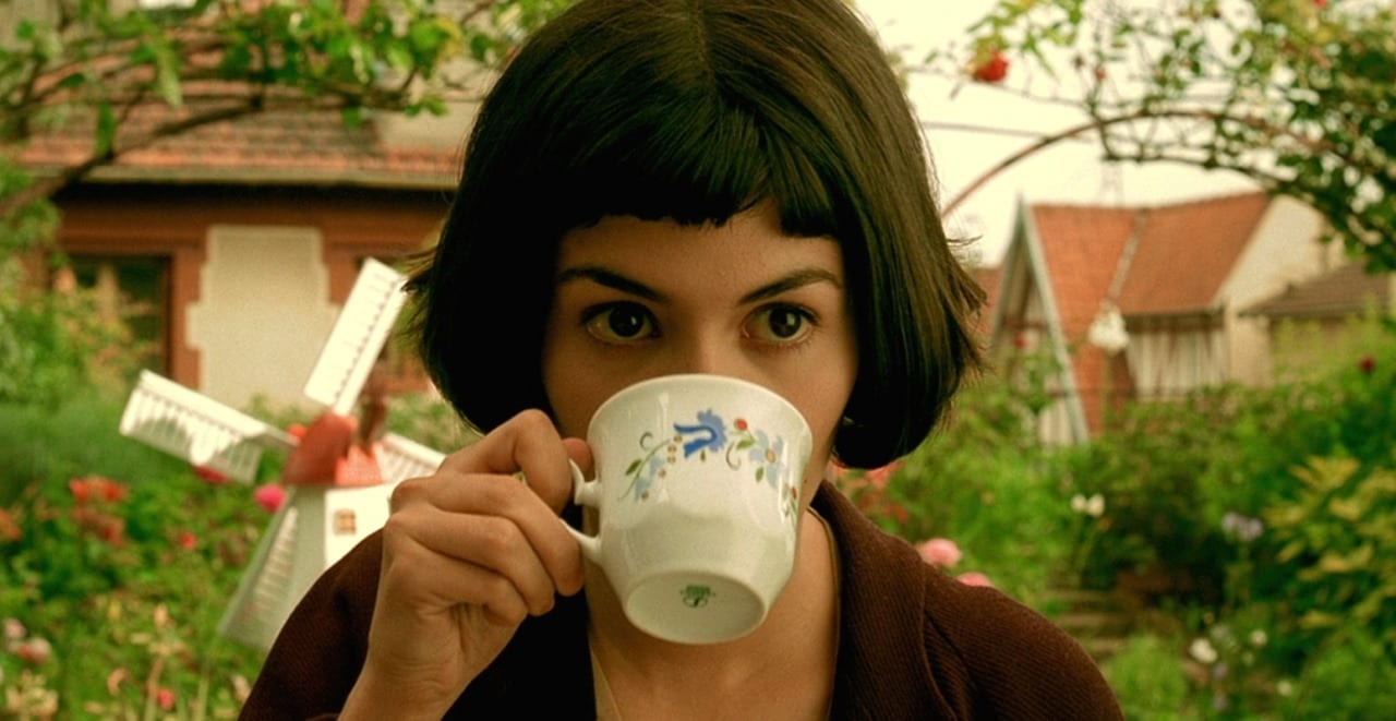 Amelie (Audrey Tautou), a white girl with dark eyes and a black bob hairstyle, holding a white teacup with a blue foral design up to her mouth. She is sitting outside in a garden, in front of a miniature windmill.